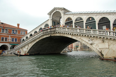 Gondolas pass under the bridge with tourists viewing the water ways & canals of Venice, Italy, Europe.