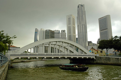 Boat crossing below Elgin Bridge with the CDB area of Singapore behind it.