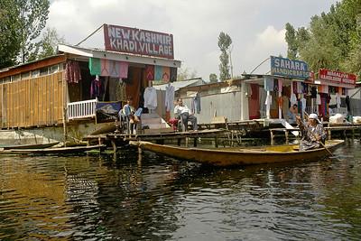 Kashmiri woman rowing her boat in front of the floating market selling handicraft & khadi items in Dal Lake, Srinagar, Kashmir, J&K, India.