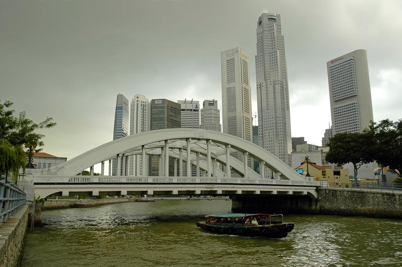 Boat crossing below Elgin Bridge with the CDB area of Singapore behind it.