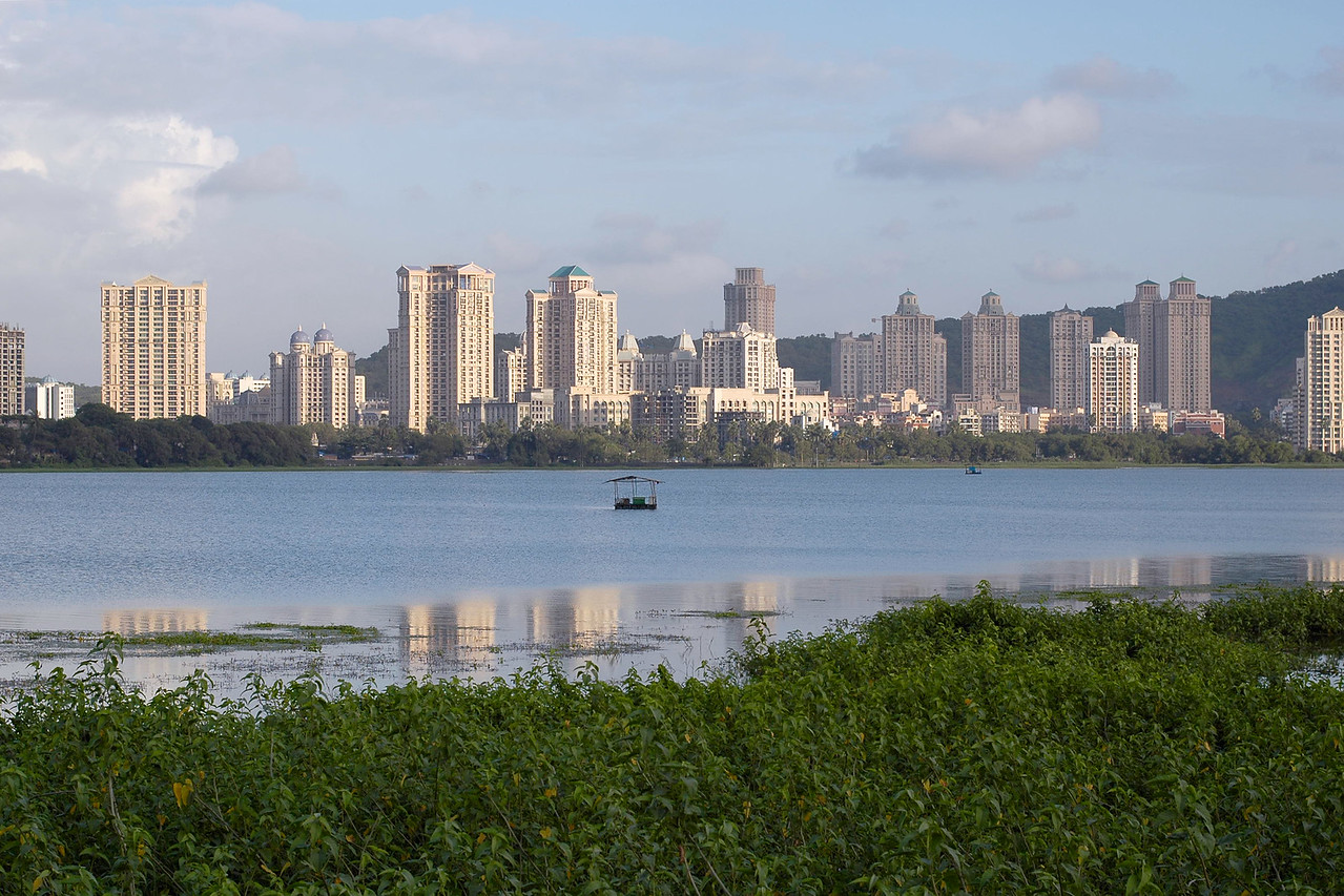 Hiranandani Gardens Complex reflecting in the Powai Lake waters. Mumbai (Bombay), Maharashtra, MH, India.