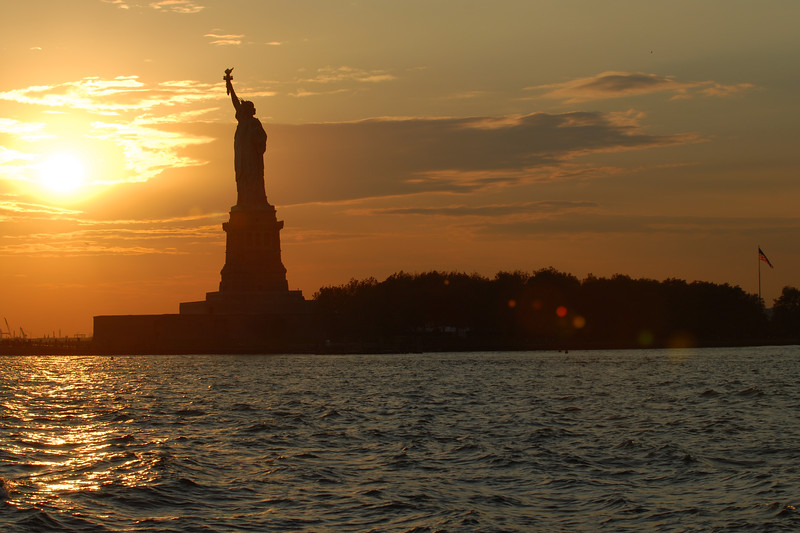 Sunset across the waters as the Statue of Liberty lady continues to stand tall on Ellis Island, New York, NY, USA.