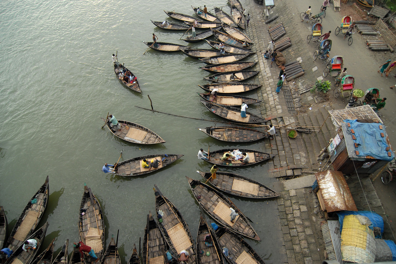 Buriganga - the life line of Dhaka, Bangladesh. Boat take people across the river. Rickshaws from there and a lot of business happens on the shores.