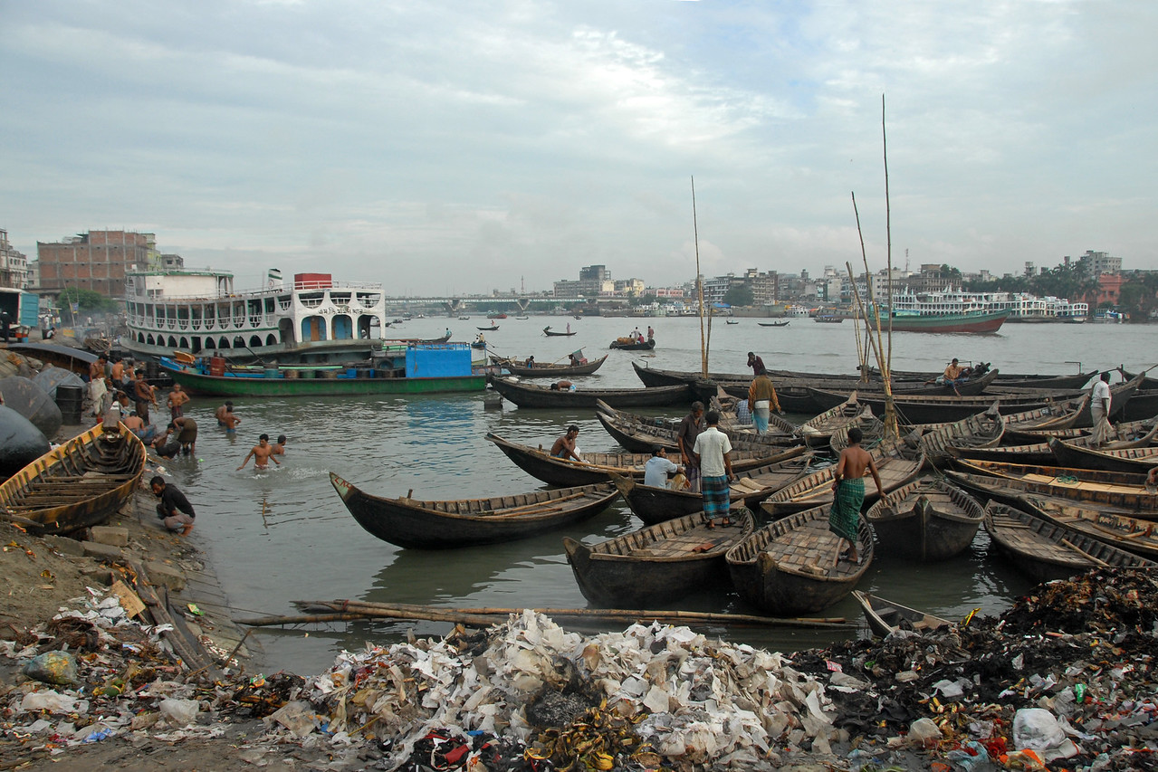 Buriganga - the life line of Dhaka, Bangladesh. Boat take people across the river. A lot happens on the shores. Washing, bathing; cleaning; relieving as well as garbage dumping. Life goes on.