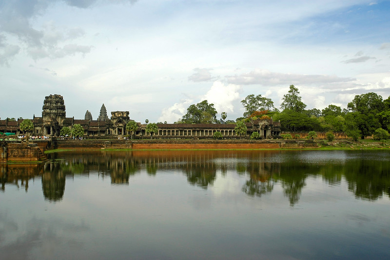 Angkor Wat temple reflecting in the waters around it as people walk over the bridge like area to enter the temple complex. Siem Reap, Cambodia