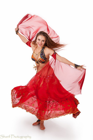 A young belly dancer makes a turn. Some motion blur, focus is sharp on the face.