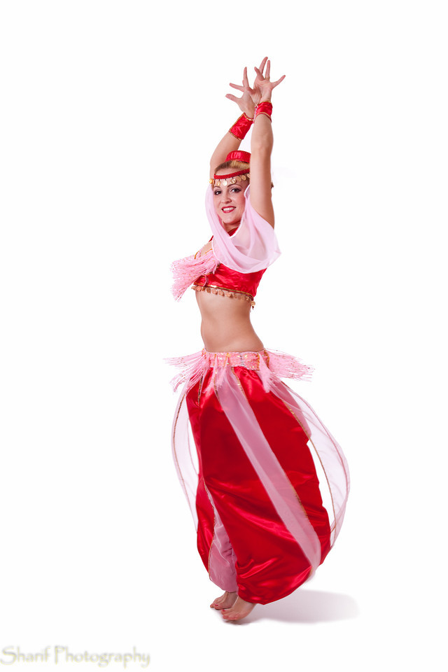 A woman dressed in a retro belly dance costume makes a turn. The face is sharp, some motion blur on the costume.