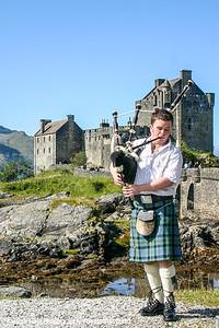 Bagpiper, Eilean Donan Castle in Dornie with Loch Duich, Scotland