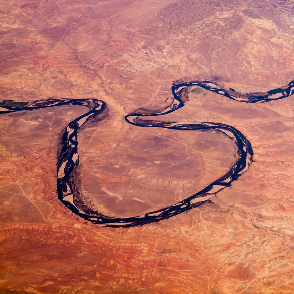somewhere over the midwest is this meandering river in a sea of red dirt.