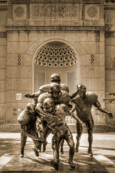 "Husker Legacy Statue outside of Memorial Stadium in Lincoln, Nebraska.  Depicting six Husker defensive players tackling a player from Kansas State, the statue was modeled after a photograph taken by Richard Voges, a photographer for the Athletic Department, during the Nebraska-Kansas State game at Memorial Stadium on Oct. 22, 1995.  ""It represents the whole attitude of Nebraska football,"".....""It emphasizes the teamwork and dedication that Nebraska football symbolizes."""