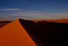 The light of the Sunset is cast over the sand dues of the Sahara in SW Libya.