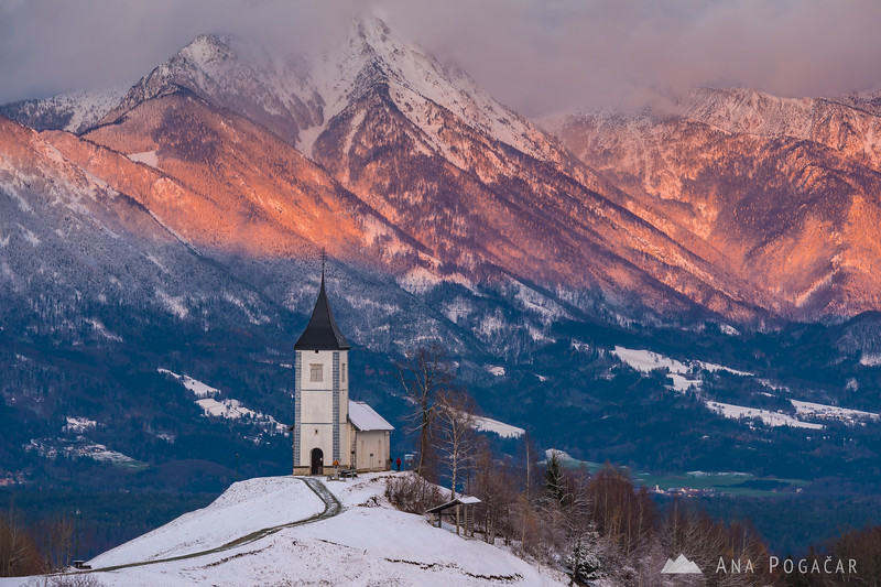 Dramatic sunset light on the slopes of Mt. Storžič behind the church in Jamnik