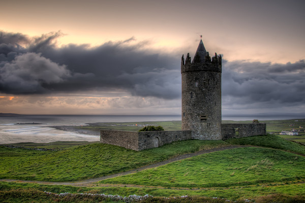 """Doonagore Castle is a round 16th-century tower house with a small walled enclosure located about 1Km above the coastal village of Doolin in County Clare, Ireland. Its name may mean """"the fort of the rounded hills"""" or the """"fort of the goats""""; it sits on a hill overlooking Doolin Point and, along with a nearby higher radio mast, is used as a navigational point by boats approaching Doolin Pier. Doonagore Castle is at present a private holiday home, inaccessible to the public.  While a castle was built on the site by Tadgh MacTurlough MacCon O'Connor from stone drawn from the quarry of Trá Leachain some time during the 1300s, the current structure is likely to date to the 16th century. It was granted to Sir Turlough O'Brien of Ennistymon (a neighboring town of Doolin) in 1582. In 1588, during the retreat of the Spanish Armada from its failed attempt to invade England, 170 survivors of a Spanish shipwreck were caught by the high sheriff of County Clare, Boetius MacClancy, and were hanged at Doonagore Castle and buried in a barrow near of Doolin called Cnocán an Crochaire."""