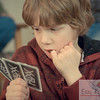 theme: the people in our lives<br /> focus: photographing faces.<br /> <br /> I was just shooting them playing cards. this one just captured his concentration. my nephew C is 7 and is so cute, he has a very expressive face and i love to photograph him.