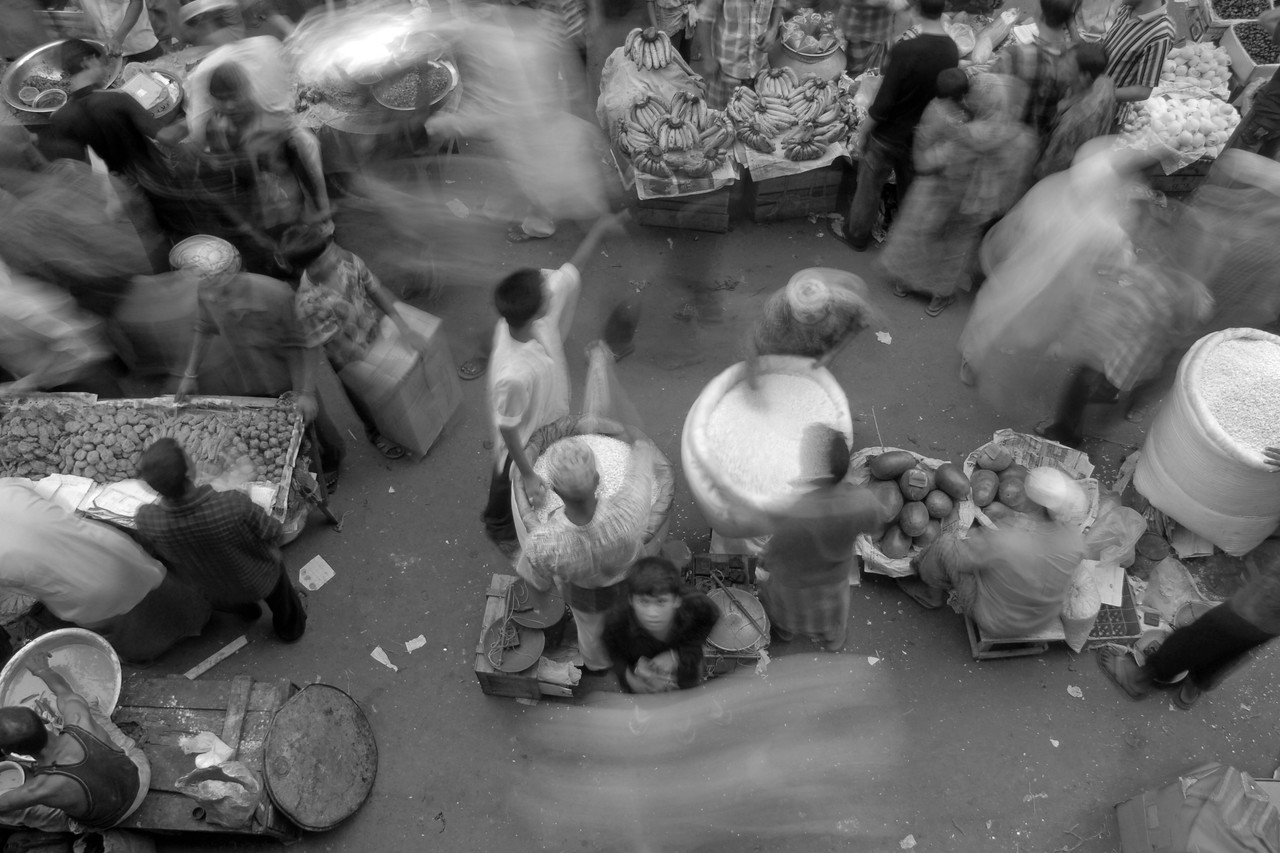 Motion blur of people going about their business in the busy bazaar.<br /> Iftar Delicacies of Dhaka. The holy month of Ramazan in the Muslim world is observed with great piety and fervour. The daylong fasting ends at sunset and the faithful break their fasting with the delicacies of IFTARI. <br /> Dhaka , particularly its densely populated older section bustles and buzzes with the rush home and the selling and buying of Iftari items as the time for Iftar draws near. Almost every restaurant of the city, from the 5-star hotels to local street outlets prepares their traditional and special Iftari items. Iftari items displayed on open-air stalls and tables with the adjacent gas burner or the stove frying Iftar items on large pans, some other in syrupy liquid and sizzling the other Iftaris over red-hot charcoal fire becomes the iconic Ramazan image of Dhaka.Chawk Bazar in old Dhaka is famous. The entire road in front of Shahi Masjid throbs with the hustle bustle. Jam packed with crowds.<br /> Top item is `Muri' (sand fried rice), and there is Piazu (paste of mashed lentils), `Beguni' or `Beson' (crushed yellow peas), `Jilapi' (sweetmeat), `Halim' (pasty broth), `Swami' and `Nargisi' Kabab with boiled egg, `Shik Kabab' (meats on skewers) as well as `dahi bara' (curd items). Dhaka, Bangaladesh