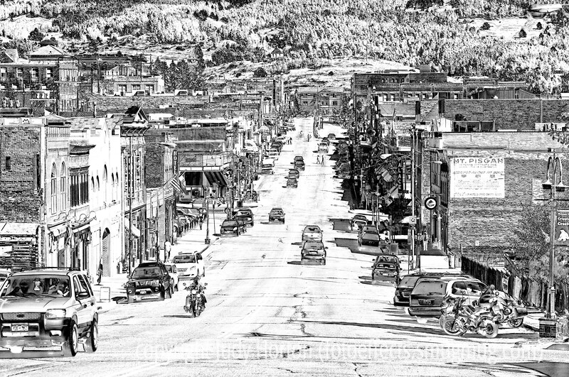 Downtown Cripple Creek, shot through a dirty windshield of a moving car.  It is a busy Sunday afternoon in Cripple Creek and most of these people are in town to gamble in the many casinos in town.  Cripple Creek is one of the main towns in Colorado which have legal gambling.  Interestingly, most of the patrons of the casinos are older folks.  I don't know if that is because they have the money or the time to gamble or whether gambling appeals more to that age group.  Most are also smokers.  Most of the casinos have placed large outdoor heaters on the sidewalks outside their facilities, so that they smokers can indulge in some degree of warmth in the winter, since smoking is not allowed inside.