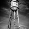 Tall  water tower with cloudy blue sky background