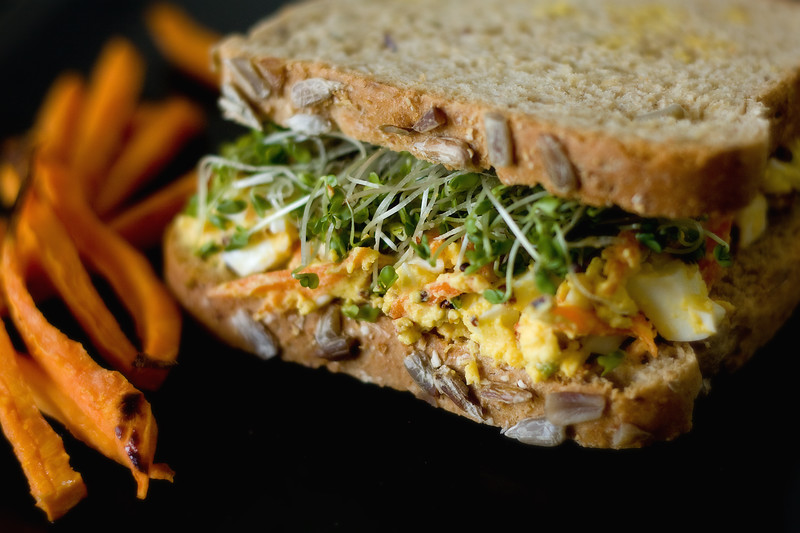Egg salad sandwich with homemade broccoli sprouts and baked sweet potato fries