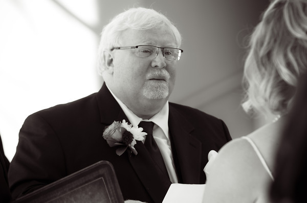 groom tears up as bride recites vows during  a fall wedding at the Clock Tower in Rockford, IL