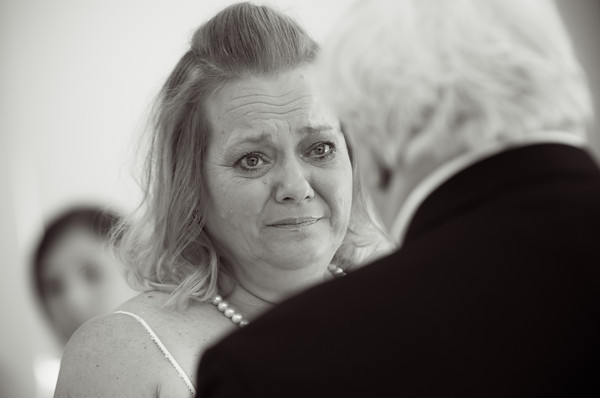 emotional bride tears up as groom recites vows during  a fall wedding at the Clock Tower in Rockford, IL