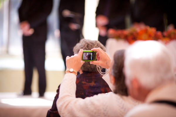 a guest takes a photo during  a fall wedding at the Clock Tower in Rockford, IL