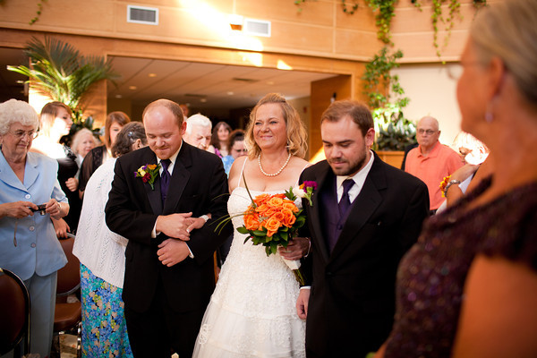 bride escorted down the aisle by her sons during a fall wedding at the Clock Tower in Rockford, IL
