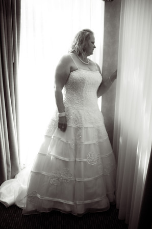elegant bride in bridal suite sneaks a peek before her fall wedding at the Clock Tower in Rockford, IL