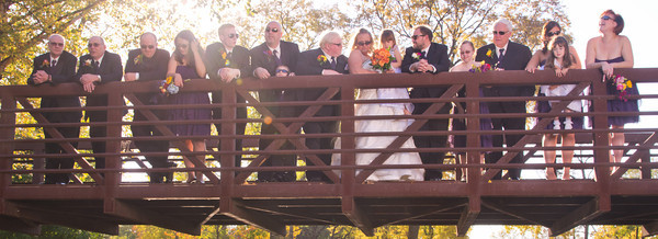 bridal party at park on a bridge outdoors following an autumn wedding at the Clock Tower in Rockford, IL