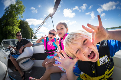 Funny faces of kids on a boat with Dad