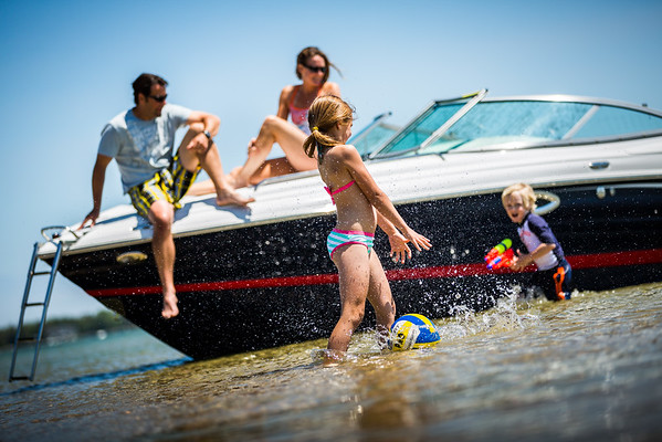 Family playing in water next to boat