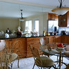 """New... """"Dining area that blends into the galley kitchen.. Beautiful all wood cabinets with solid maple doors & drawers accented with brown glaze.  New granite counters & tile back splash."""