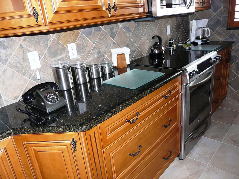 """New... """"Open-feel"""" galley style.. Beautiful all wood cabinets with solid maple doors & drawers accented with brown glaze.  New granite counters & tile back splash."""