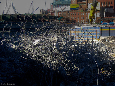 Twisted rebar from the demolition of the central artery. (February 1, 2004)  The new Zakim bridge is seen in the distance.