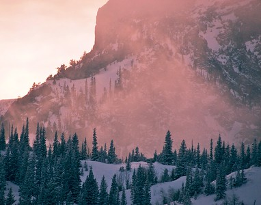 Blowing snow colors the air around Hallet Peak on a January evening in Rocky Mountain National Park.