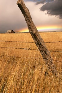 An autumn rainbow and an old fencepost, near Westcliffe, Colorado.  Had to wait here for a while for some foreground light to bring out the texture on the post and in the grass, all the while hoping the rainbow would persist.