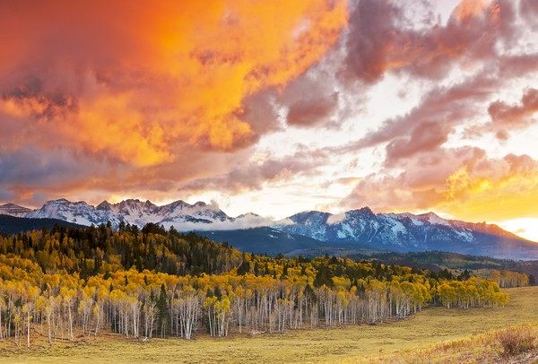 The Sneffels Range at sunset, early October 2009.  The weather a few days before was not kind to the autumn leaves; most went from green straight to brown.  But there were definitely a few protected spots that kept some good color, like these trees, lit by the glowing clouds above.  I spent most of this day riding my bike, with the snow stopping and starting every hour or so.  Luckily the weather broke with about an hour to go until sunset.