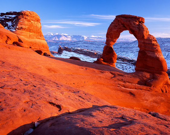 Delicate Arch, Utah, in Arches National Park at sunset on New Year's Eve 2008.  I love going to Arches in the winter!  The crowds are gone, the snow in the north shadows is beautiful, and I'd personally rather hike in 30F than 100F.  It had been a pretty hazy day, but around 3:30 the western skies started to clear up, setting up great light for sunset.  Shot on Fuji Velvia 100 4x5 film.