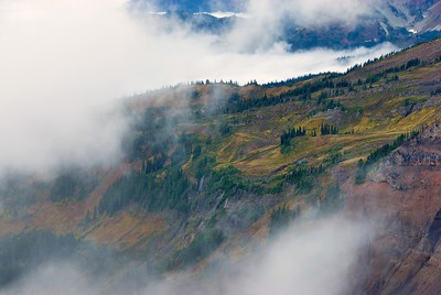 The hillsides in the fog at Mount Rainier show their changing colors in autumn