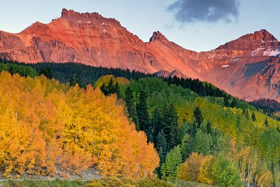 Changing aspens and red mountains at sunset, shot from Trout Lake, Colorado