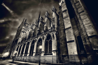 "The Notre Dame.Paris  Snow. I swore I saw Quasimodo. Right there... look! Between those parapets. Dang, he's quick. Cue the scary music.  This night, I set up and took aim at the side of the Notre Dame Cathedral. The ghosts of writers, emperors, members of the clergy and Victor Hugo all looking on, or so it felt. I apologized to them for swearing so prolifically as huge gobs of snow landed on my lens, blurring up my perfect shot du arte. It always landed on the best shot. Grrrr. I shoulda planned better. Clearly, I didn't. It doesn't look like it was snowing that much - you can only sorta see it in the light on the upper left - but trust me, it was and I was soaked. My surly, potty-mouthed self was determined to walk away victorious and I would have stood there all damn night if I had to. Much to my HUGE relief, I didn't have to.   I left the lens distortion, a couple of blurrrrrs. The skew fit the mood, told the the story, covered the sense ""surreality"" I felt standing there that night.   I hope Victor Hugo would approve. But I think he was cranky. So I'll just have to approve of myself. ;-))  ©Karen Hutton - Creative Commons (CC BY-NC 3.0)"