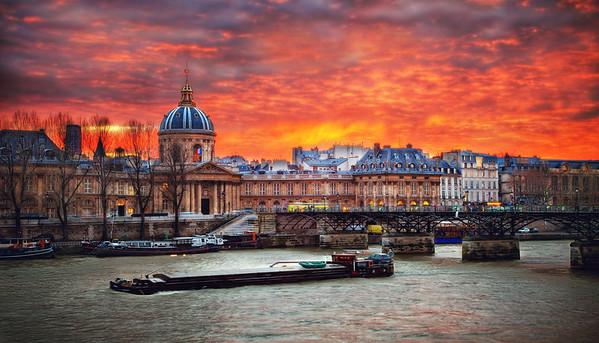 "InSeine Sunset My first time in France, first gaze upon the Seine river - and first full view of this gorgeous city so full of art, history and promise. It even had proper lighting, which I thought was very considerate. Just heavenly! So I made it look the way it felt.  I couldn't believe this sunset. People said it was unusual, but it was my first time in Paris, so how would I know? The thought did cross my mind; ""Gee, it's just like the Glenshire Pond!"". Then realized I'd probably committed some kind of mental crime de comparison.    The bridge is the Pont des Arts. It was a tit bit nippily in December when we were there. Snapping this shot in all my layers and full length down coat I could hardly imagine it - but during the summer it becomes a ""studio en plein air"" - a spot for painters, photographers, and other artists, and a picnic grounds for locals.   Hey - let's go there then! Wanna?    ©Karen Hutton - Creative Commons (CC BY-NC 3.0)"