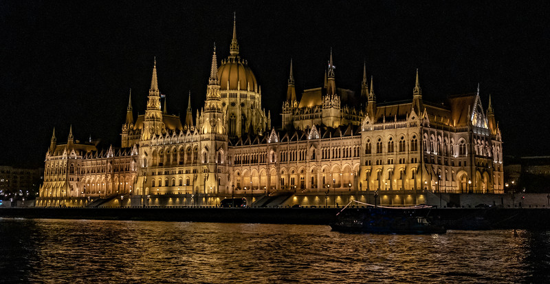 The Parliament Building At Night Seen From The Danube River.