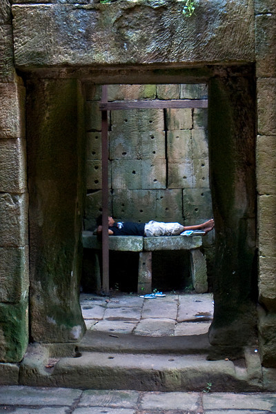 ANGKOR. BAPHUON. CARD SELLER TAKES A NAP INSIDE THE ENTRANCE GATE. SIEM REAP.