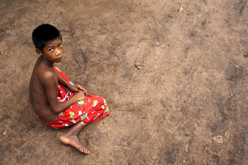 CAMBODIAN BOY DRAWS A FACE IN THE SAND. PREAH KHAN. ANGKOR. SIEM REAP. CAMBODIA.