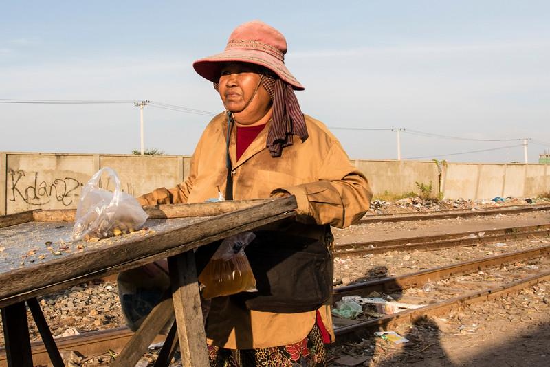 PHNOM PENH. SLUM NEAR THE RAIL TRACK. KHMER WOMAN WALKS WITH HER PSUHCART.