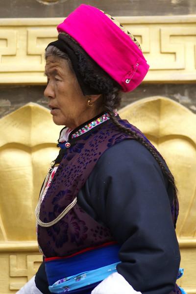 SHANGRI-LA. OLD TIBETTAN LADY PRAYER ALONG THE BIGGEST PRAYER WHEEL IN THE WORLD. YUNNAN.