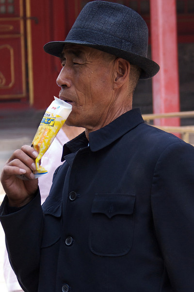 BEIJING. FORBIDDEN CITY. OLD CHINESE MAN DRINKING.