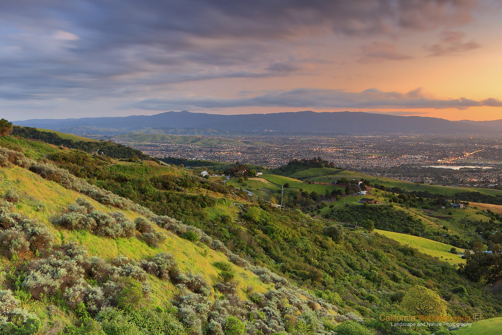 """Valley View""<br /> Location: South Bay Hills, California.<br /> <br /> View of the valley from the hills that surround it is always enjoyable. After I got off work one day in spring I headed to Mt. Hamilton road and saw this incredible view when the city lights were turning on and sun had just set. Moreover, spring time green on the hills is my favorite and passing storm clouds added that extra bonus to the view.<br /> <br /> Tech Info:<br /> Lens: Canon EF 24-70 f/2.8L @ 38mm<br /> Camera: Canon EOS 5D Mk II<br /> Exposure: 135sec at f/14 and ISO 50<br /> Filters: LEE ND Grads 0.6 and 0.9 soft edge stacked together"