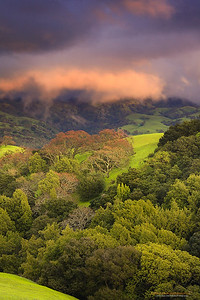 """Sunset and the Raingods"" Location: Calaveras Hills, Milpitas, California.  Storms in California have a very transient nature. The sky can be very dark at one moment and a clear blue the next; but somewhere in between are these magical fleeting moments that are fun to capture.  Fortunately I happened to catch one such moment today evening. As I got off from work I saw some great light over the Calaveras hills which are just a few minutes away from where I live. The sunlight was reaching the storm clouds at a low angle and illuminating just the low lying layers of the clouds giving this fiery effect.  This show of light and dark was truly transient. A minute later the sunset glow was gone and it was all but a dull gray sky.  Tech Info: Lens: Canon EF 70-200 f/4L IS @ 93mm Camera: Canon EOS 5D Mk II Exposure: 4sec at f/10 and ISO 50 Filters: B+W Circular Polarizer, LEE ND Grads 0.6 and 0.75 soft edge stacked together Single exposure with no HDR treatment"