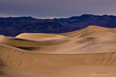 """Mesquite Sand Dunes"" Location: Death Valley National Park, California.  I always wanted to photograph the lines and patterns that form in sand dunes. So when I visited Death Valley I liked this spot from where sharp edges were looking well with the smooth undulations of the dunes and leading quite nicely to the mountains behind.  Tech Info and Tip: Lens: Canon EF 70-200 f/4L IS @ 97mm Camera: Canon EOS 30D Exposure: 1/125sec at f/8 and ISO 100 Filters: No filters  I typically prefer not to shoot during mid day lighting conditions, however, this particular shot came out nice even though it was shot during mid day conditions. Death Valley has such unique landscape that defies imagination. A visit here is the closest thing to vising an alien landscape. It is one of the most popular locations to photograph. Its badlands, sand dunes, salt pans, strange racetracks offer unique opportunities to capture its beauty."